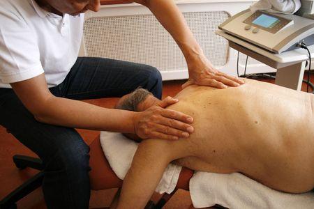 Physiotherapist massaging shoulder photo