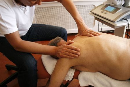 old man on a physical pressure: Physiotherapist massaging shoulder