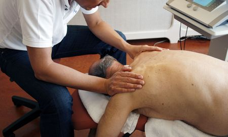 old man on a physical pressure: Physiotherapist massages muscles of senior patient Stock Photo