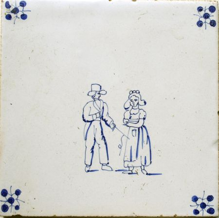 seventeenth: Antique seventeenth century Delft blue and white tyle. Image of a Dutch woman and man. Man in costume and hat, woman in typical Dutch farmers costume