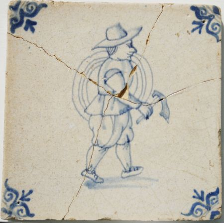 seventeenth: Antique and cracked seventeenth century delft blue and white tile. The image is of a Dutch farmer