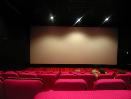 few: blank screen in cinema with pink chairs and a few viewers