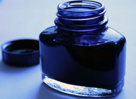 blue ink in an open blue inkpot with blue background  photo