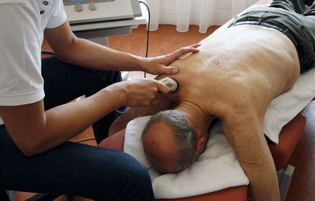 strength therapy: physiotherpist works with ultrasound on senior patient Stock Photo