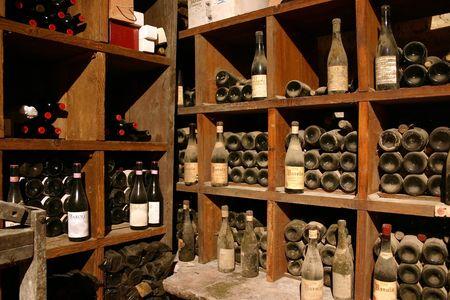 ancient wine bottles gathering dust in italian wine cellar