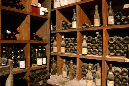 dusty: ancient wine bottles gathering dust in italian wine cellar