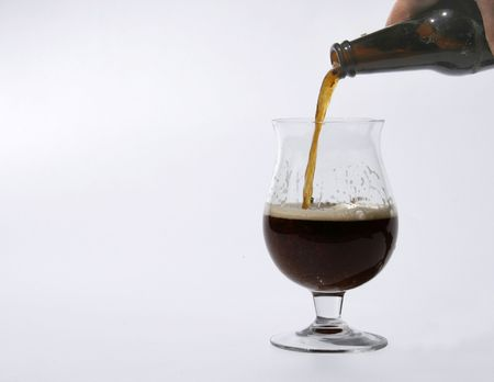 intoxicating: a big glass is filled with dark beer+ Stock Photo