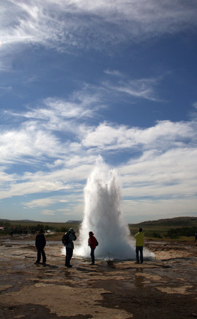 Geyser Strokkur on Iceland erupting hot water and steam, series of shots of the erupting geyser fontain, from the beginning to the end.  Hot water is erupting high in the air photo