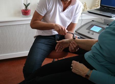 physical test: Il fisioterapista utilizza il martello per verificare i riflessi sulla donna