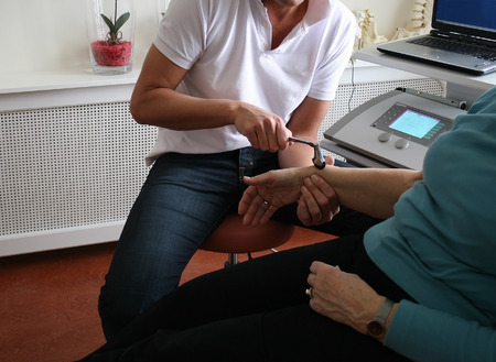 treating: Physiotherapist uses hammer to test reflexes on woman Stock Photo