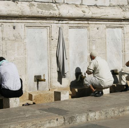 religious men washing feet before entering mosque photo