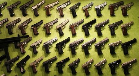 All kinds of different handguns displayed on green background for sale  Stock Photo - 1808083