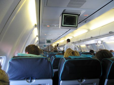 Abteile: Passagiere sitzen und zu Fu� in einem Flugzeug