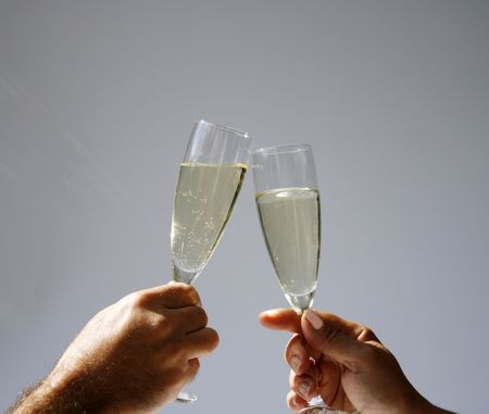 two hands with champagne flutes toasting in sun