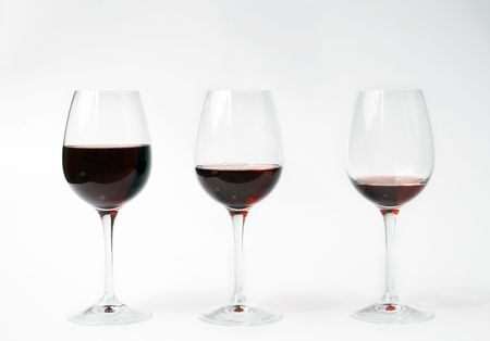 three glasses of red wine filled in different levels. Full, half full, almost empty. Stock Photo