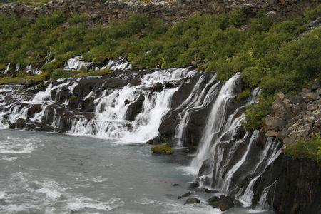 Hraunfossar, Borgarfjordur, Iceland. Underground river ends through lava as a waterfall into a wild river. photo