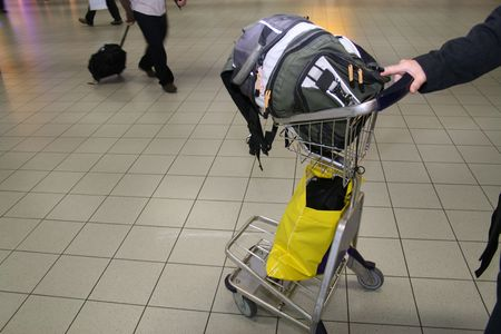 dolly bag: man pushing hand cart in airport with backpack on it