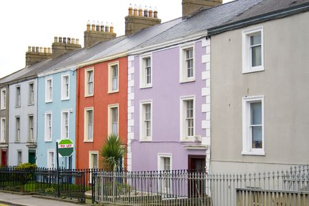 to let: Colorate case su una riga in una strada di Dublino con un segno per far fronte di uno di loro Archivio Fotografico