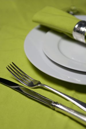 table setting with plates, napkin, silverware and glass on apple green table cloth photo