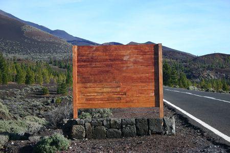 volcanic landscape: blank wooden sign next to asphalt road in volcanic landscape