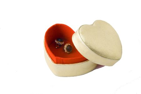 heart shaped box with red inlay and expensive golden earrings isolated on white photo