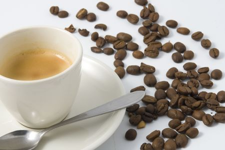 white cup with espresso and coffeebeans