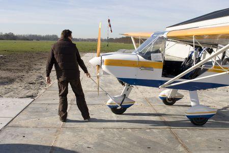 airplane ultralight: Pilot pulls ultralight airplane from hangar Stock Photo