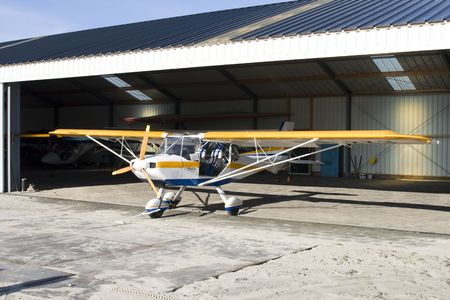 yellow and blue ultralight plane in hangar photo