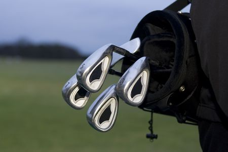 black golfbag with clubs hanging out on back of golfer