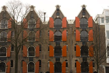 Old warehouses converted to homes with red shutters in Amsterdam