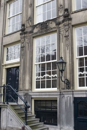 typical vintage classic house on canals in Amsterdam with big stairs windows, and lantern photo