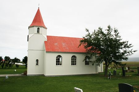 very simple wooden church in Iceland with small cemetary and tree photo