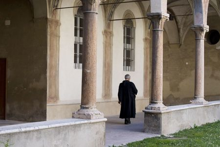 priesthood: Italian medieval convent in Parma with priest walking in loggia