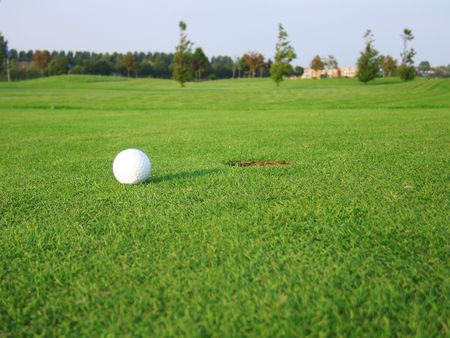 Golf ball on green near hole photo