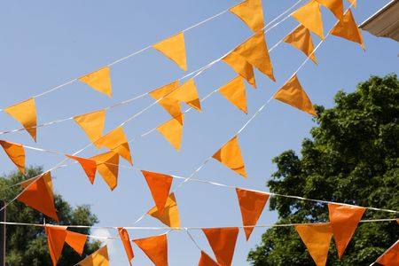 orange flags hanging outside against a blue sky. (Often used at queens day in the netherlands) photo