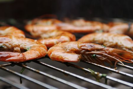 prep: Close up of fresh orange prawns on grill of barbecue