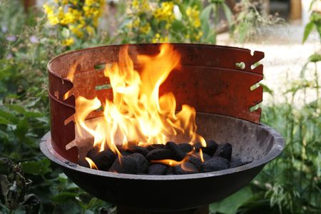Golden red flames in barbecue standing in garden Stock Photo - 3345753