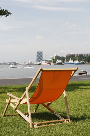 maas: Orange deckchair on grass in Rotterdam with view on busy river Maas and harbor. Docks and cranes in background