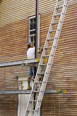 Man standing on scaffold wood sanding the exterior of a house photo