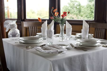 ware: Classic table setting with white tablelinen, napkins and red flowers