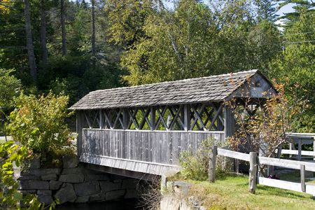 Beautiful wooden covered bridge in rural landscape photo