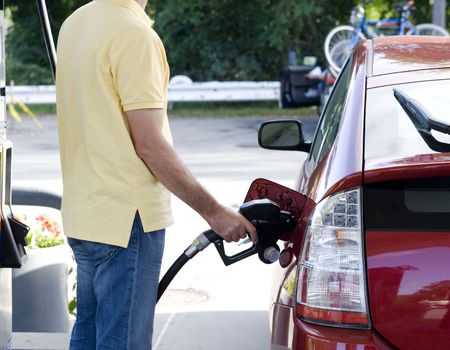 unleaded: Man standing at petrol tank and is filling up his red car Stock Photo