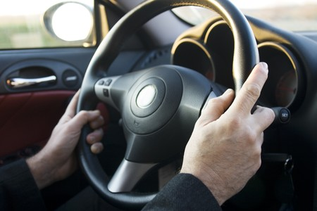 male hands on steering wheel of car photo