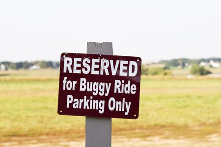 amish buggy: Sign on wooden post with text: reserved for Buggy Ride Parking olnly Stock Photo
