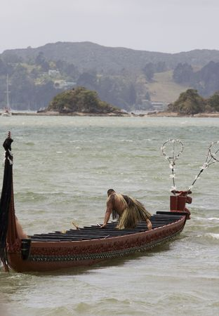 A typical Maori Waka (war canoe) with one Maori man in traditional clothing stepping in. Stock Photo - 4662483
