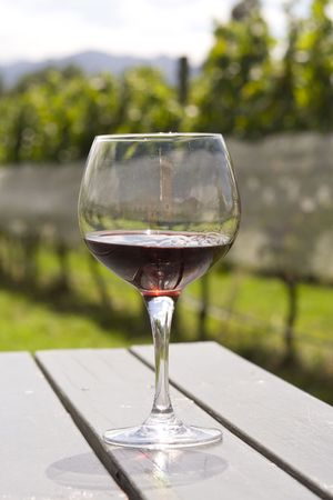 Wineglass with red wine standing on wooden table in vineyard in Hawkes bay in New Zealand photo