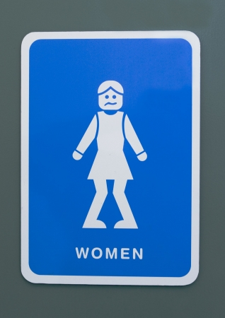 Funny toilet sign of a woman with knees pressed together