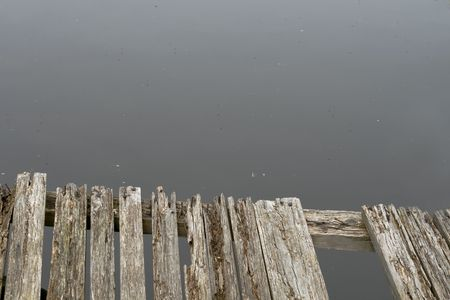 grey water: Old grey wooden boardwalk above grey water Stock Photo