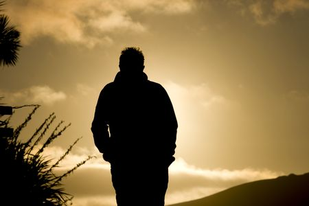 backside: Man walking in sunset with hands in pocket. Black silhouette against sunlight