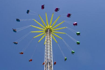 Colorful carts on a giant chain swing high up in the sky photo